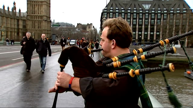 tourism in london bagpipe player on bridge with houses of parliament in background sot / houses of parliament seen through westminster bridge / gv... - bagpipes stock videos & royalty-free footage
