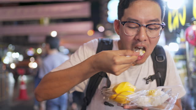 tourism man eating mango sticky rice is a traditional thai dessert made with glutinous rice, fresh mango and coconut milk, and eaten with a spoon or sometimes the hands. - tray stock videos & royalty-free footage