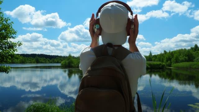 vídeos y material grabado en eventos de stock de turístico solo en un tranquilo lago - camiseta blanca