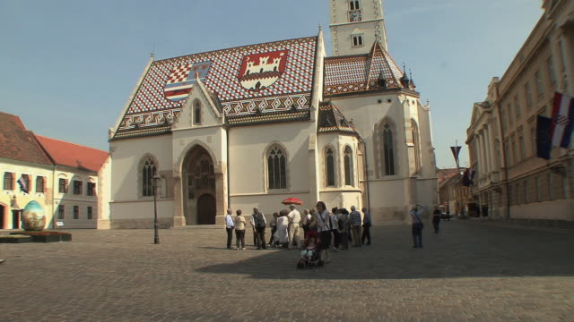 ws tourist and guide in front of st mark's church in upper town / zagreb, croatia  - zagreb stock videos and b-roll footage