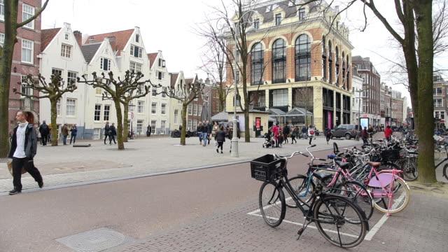 stockvideo's en b-roll-footage met toeristische en straat verkeer tram & boten bij amsterdam amsterdam, nederland - standbeeld