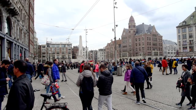 tourist and street traffic tram & boats at amsterdam central station  amsterdam, netherlands - statue stock videos & royalty-free footage