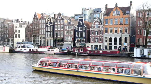 tourist and street traffic tram & boats at amsterdam central station  amsterdam, netherlands - amsterdam stock videos & royalty-free footage