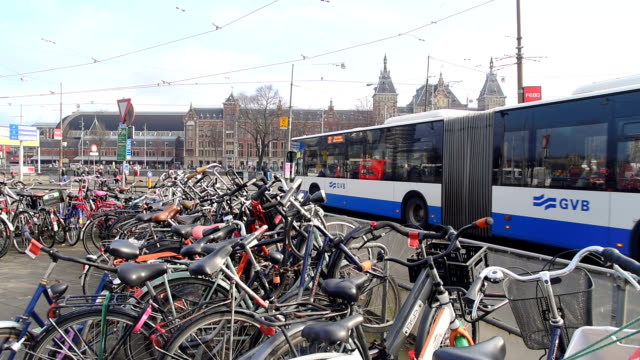 tourist and street traffic tram & boats at amsterdam central station  amsterdam, netherlands - stazione video stock e b–roll