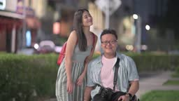 Tourist asian chinese man with wheelchair and his female friend looking at camera smiling