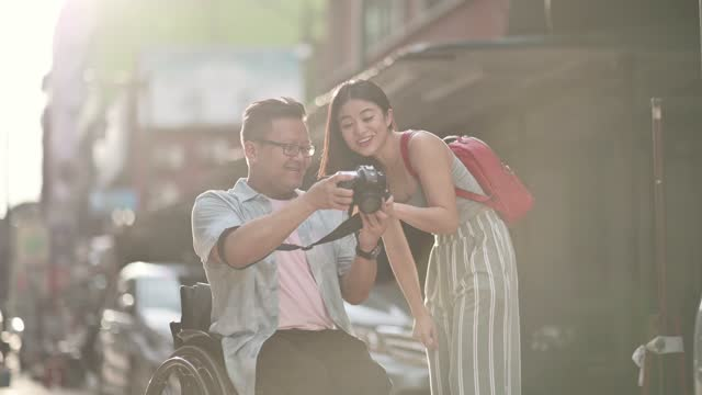 tourist  asian chinese man with wheelchair showing checking camera device screen what they photographed at petaling street, kuala lumpur during sunset - accessibility stock videos & royalty-free footage