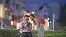 Tourist asian chinese man with wheelchair showing checking camera device screen what they photographed at petaling street, kuala lumpur