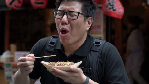 tourist asian man feeling very hot when he eating takoyaki, ball-shaped japanese snack - japanese food stock videos & royalty-free footage