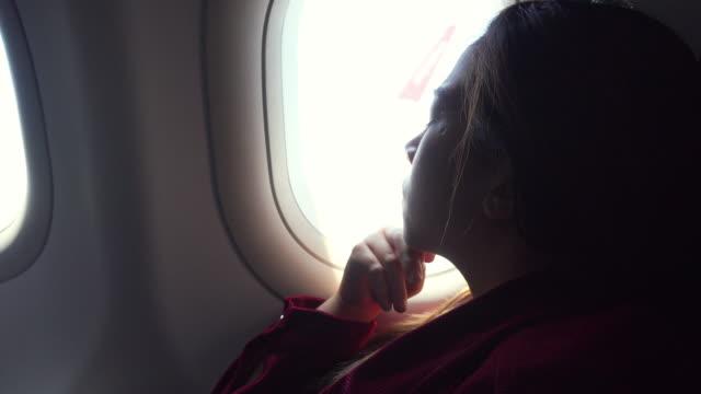 vidéos et rushes de femme asiatique de touriste regardant la fenêtre d'avion pendant le vol - première classe