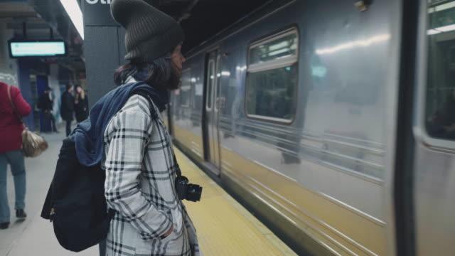 stockvideo's en b-roll-footage met toeristische aziatische vrouw te wachten de trein op metro platform. - metro platform