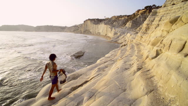 tourist at scala dei turchi at sunset, rossello cape, realmonte, agrigento, sicily, italy, europe - sicily stock videos and b-roll footage