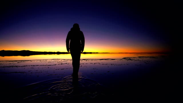 tourist at sunrise viewing salar de uyuni bolivia - ウユニ塩湖点の映像素材/bロール