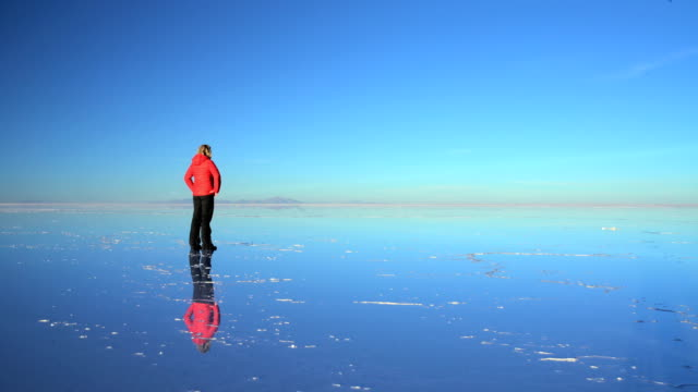 tourist at sunset viewing bolivian salar de uyuni - unendlichkeit stock-videos und b-roll-filmmaterial
