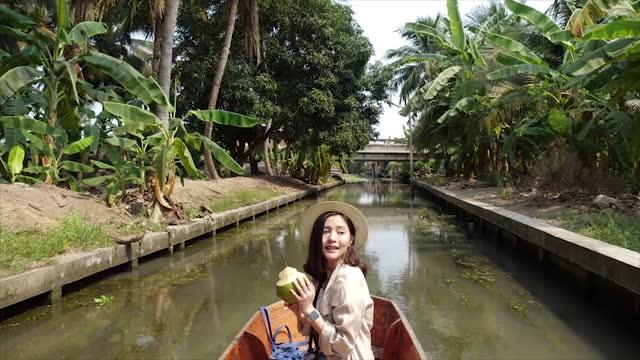 tourist schöne asiatische frauen sind reisen lokale wahrzeichen thailand.touristen machen tour von holzbooten und fotografieren und essen lokale lebensmittel am damnoen saduak floating market, thailand, berühmtes touristenziel. - nur junge frauen stock-videos und b-roll-filmmaterial