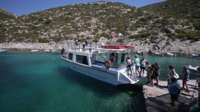 stockvideo's en b-roll-footage met tourist board a sightseeing boat which takes them to navagio , shipwreck beach on zakynthos island, greece. the beach of navagio with the old... - griekenland