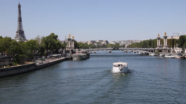 tourist boat moves on the seine before passing under the pont alexandre iii, with the eiffel tower in the distance, on july 21, 2020 in paris,... - ausflugsboot stock-videos und b-roll-filmmaterial