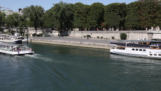tourist boat on the seine heads towards the pont des invalides, in the center of the capital city, on july 21, 2020 in paris, france. batobus and... - ausflugsboot stock-videos und b-roll-filmmaterial