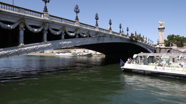 tourist boat on the seine just passes under the pont alexandre iii, in the center of the capital city, on july 21, 2020 in paris, france. batobus and... - ausflugsboot stock-videos und b-roll-filmmaterial