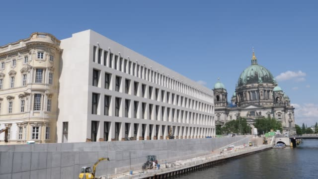 a tourist boat on the spree river next to the baroque and modernist facades of the humboldt forum as the dom cathedral stands behind on june 17 2019... - スプリー川点の映像素材/bロール