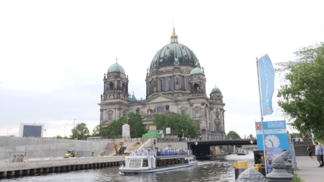 a tourist boat passes by the construction site of the berliner schloss city palace which will contain the humboldt forum foundation and museum on... - berliner stadtschloss stock-videos und b-roll-filmmaterial