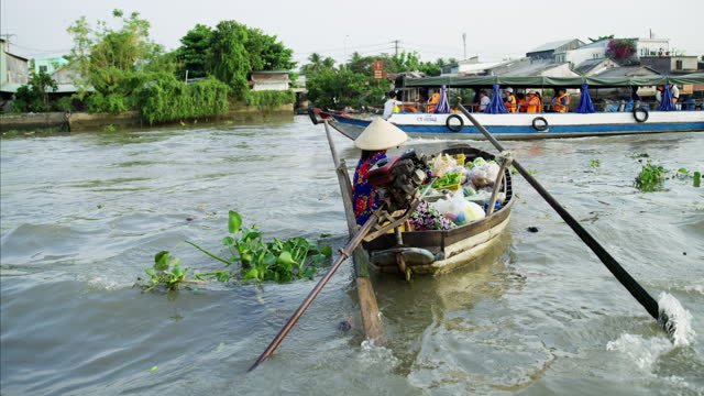 tourist boat passing female floating market vendor vietnam - local politics stock videos & royalty-free footage