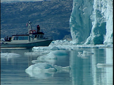ws pan tourist boat traveling along calving glacier, greenland - ausflugsboot stock-videos und b-roll-filmmaterial