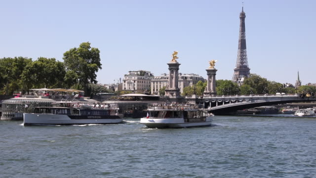 tourist boats are crossing each other along the seine, with the eiffel tower and the pont alexandre iii in the distance, on july 21, 2020 in paris,... - ausflugsboot stock-videos und b-roll-filmmaterial