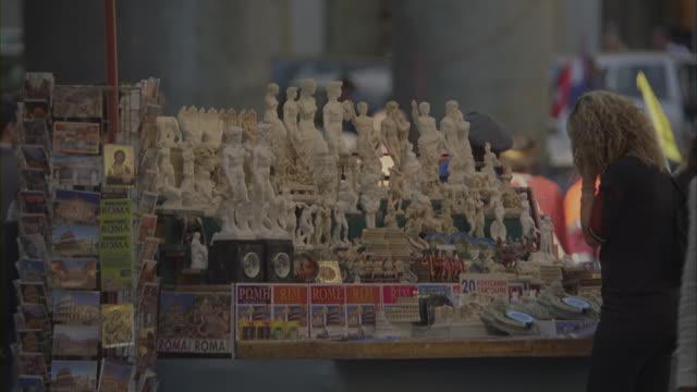 a tourist browsing through figurines at a souvenir shop. - ricordi video stock e b–roll