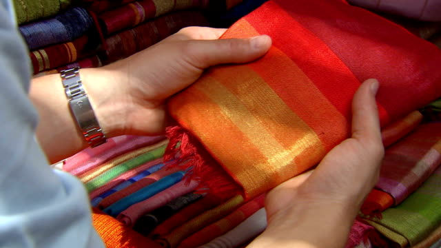 tourist buying orange and red silk scarf from stall at souk, muscat, oman - scarf stock videos & royalty-free footage