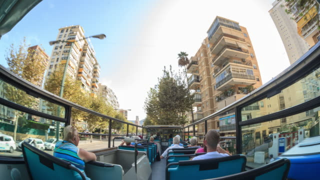 stockvideo's en b-roll-footage met tourist city bus travels around the city of benidorm - dubbeldekker bus