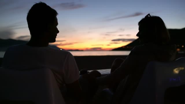 vidéos et rushes de couple de ms touristiques bénéficiant d'océan coucher de soleil vue sur patio - balcon