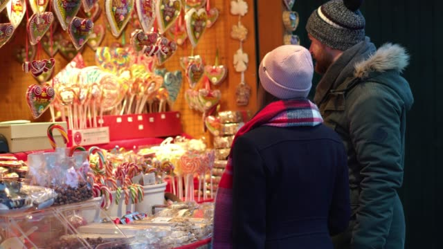 tourist couple having fun at christmas market - mercato all'aperto video stock e b–roll