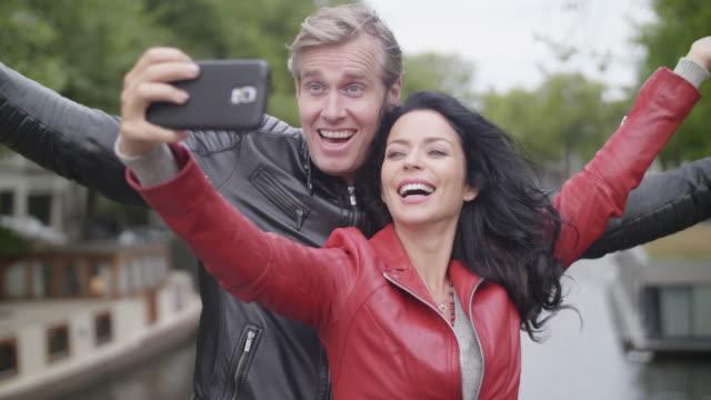 tourist couple in amsterdam - coppia di adulti di mezza età video stock e b–roll