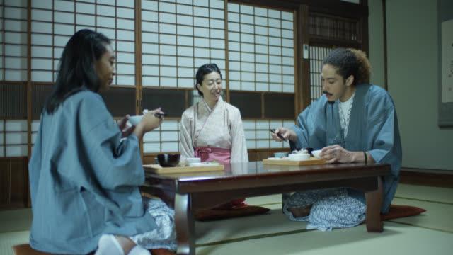 stockvideo's en b-roll-footage met toeristisch koppel in yukata geknield aan tafel om te eten in ryokan - ryokan