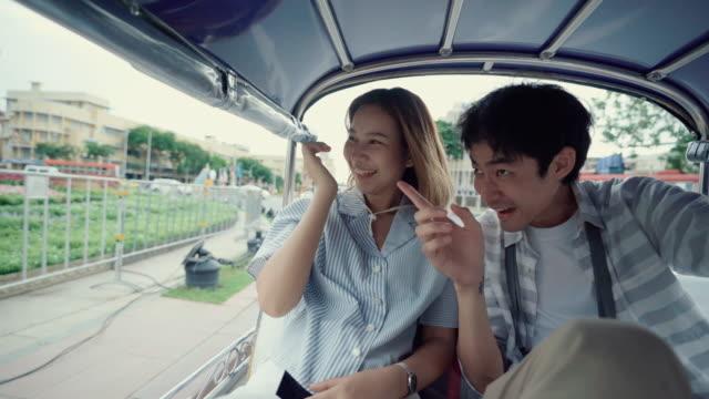 tourist couple riding tuk tuk in bangkok - auto rickshaw stock videos & royalty-free footage