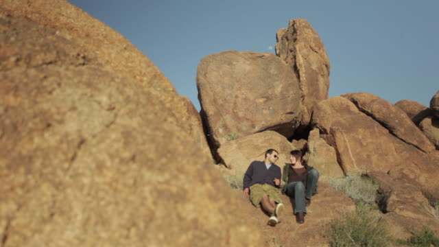 ws pan tourist couple sitting by rock / palm springs, california, usa - legs crossed at ankle stock videos and b-roll footage