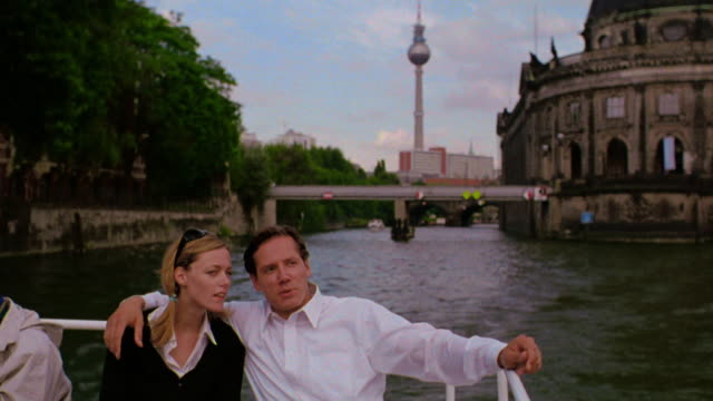 pan tourist couple sitting in boat on spree river talking with bode museum in background / berlin, germany - city break stock videos and b-roll footage