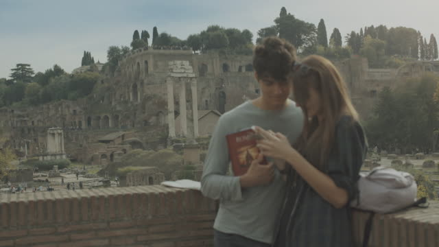 Tourist couple social networking by the Roman forum in Rome