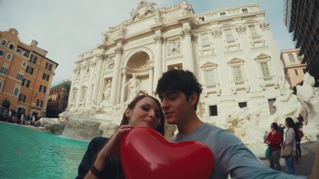 Turist par tar en selfie på Fontana di Trevi med hjärta