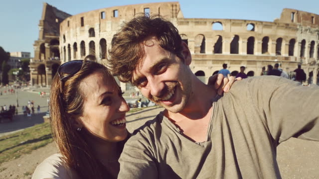 coppia turistico prendendo un selfie davanti al colosseo - selfie video stock e b–roll