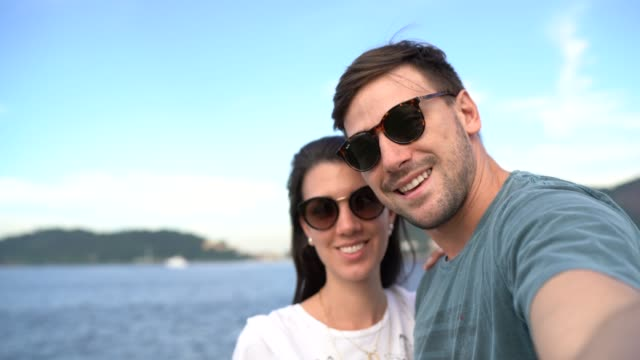 tourist couple taking a selfie in front of the sea - sunglasses stock videos & royalty-free footage