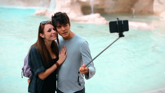 Tourist couple taking a selfie stick in Rome
