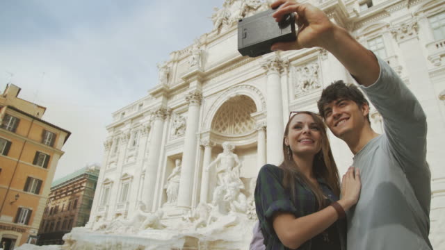 Tourist couple taking a selfie with vintage instant camera