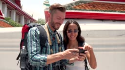 Tourist couple taking selfie with smartphone at Thai temple in Thailand