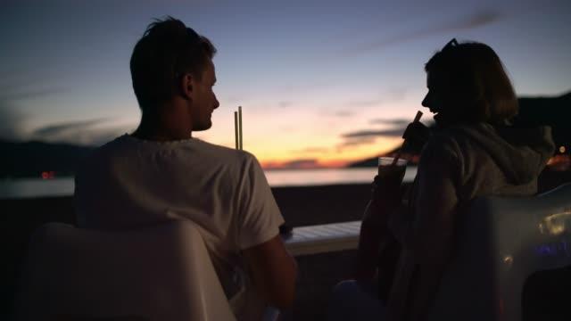 vídeos de stock, filmes e b-roll de casal ms tourist brindando, desfrutando de cocktails no pátio com vista para o mar ao entardecer - sacada