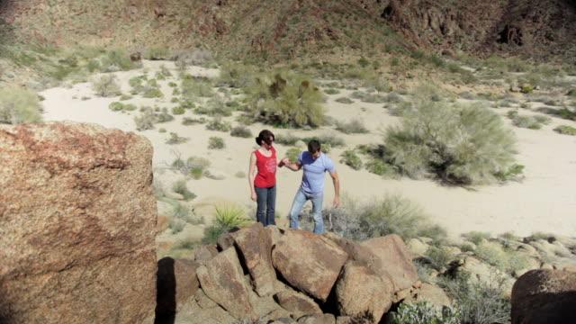 WS Tourist couple walking over boulder / Palm Springs, California, USA