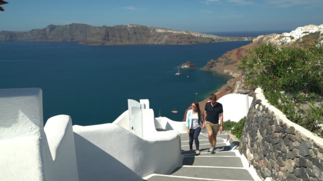 tourist couple walking up path on santorini island - greece stock videos & royalty-free footage