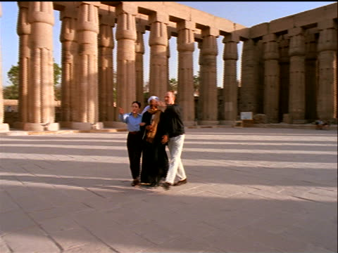 vídeos y material grabado en eventos de stock de pan tourist couple walking with male egyptian guide through temple ruins / temple of luxor / egypt - mujer con grupo de hombres
