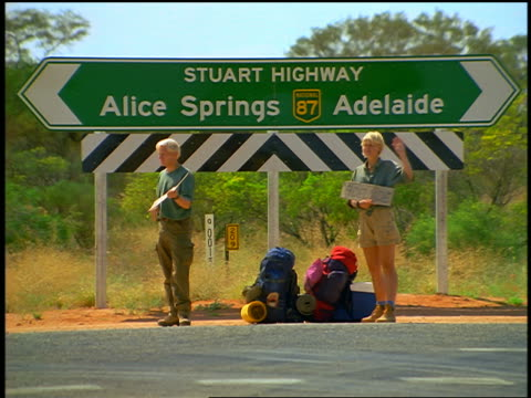 tourist couple with backpacks hitchhiking standing beneath road sign / northern territory, australia - ヒッチハイキング点の映像素材/bロール