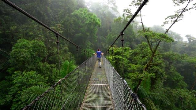 stockvideo's en b-roll-footage met tourist crossing a hanging bridge in arenal national park, rainforest - costa rica